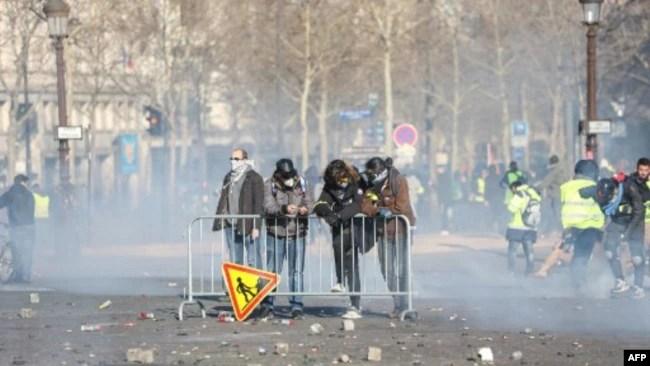 Los manifestantes están detrás de una cerca durante los enfrentamientos con las fuerzas de la policía antidisturbios en los Campos Elíseos en París