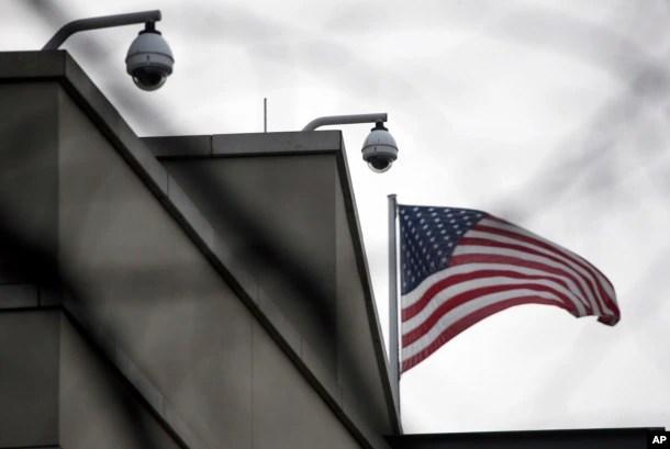 American flag waves beside CCTV cameras on top of the U.S. embassy in Berlin, Germany, Oct. 25, 2013.