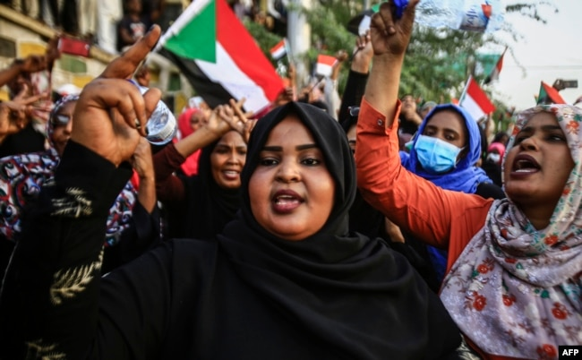 Sudanese women chant slogans during a demonstration demanding a civilian body to lead the transition to democracy, outside the army headquarters in the Sudanese capital Khartoum on April 12, 2019.