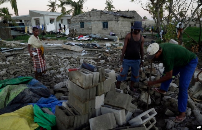 Members of a church salvages bricks from a damaged church building in Beira, Mozambique, Monday, March 25, 2019. The United Nations is making an emergency appeal for $282 million for the next three months to help Mozambique start recovering from the devastation of Cyclone Idai.