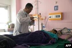 Perdana Menteri Bhutan Lotay Tshering merawat seorang pasien di Rumah Sakit Rujukan Nasional di ibu kota Bhutan, Timphu, 30 Maret 2019.