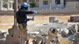 FILE - This Wednesday, Aug. 28, 2013 citizen journalism file image shows a member of UN investigation team taking samples of sands near a part of a missile that is likely to contain chemicals, according to activists, in Damascus countryside of Ain Terma, Syria.