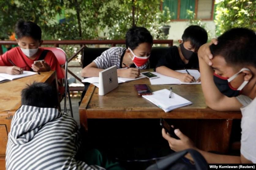 Dimas Anwar Saputra, seorang siswa SMP, bersama teman-temannya memanfaatkan jaringan internet gratis di kantor kelurahan untuk belajar di tengah pandemi COVID-19, di Jakarta, 9 September 2020. (Foto: Willy Kurniawan/Reuters)