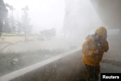 A journalist braves high waves at Heng Fa Chuen, a residential district near the waterfront, under Typhoon Mangkhut attack in Hong Kong, China, Sept. 16, 2018.