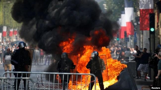Un inodoro portátil se quema junto a los gendarmes franceses durante los enfrentamientos con manifestantes en la avenida de los Campos Elíseos, en París, Francia, el 14 de julio de 2019. REUTERS.