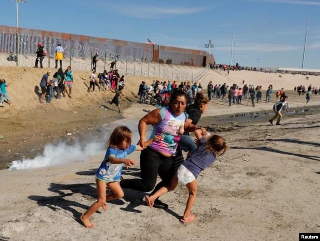 Una familia de migrantes, parte de la caravana de miles que viaja desde Centroamérica hacia Estados Unidos, corre para escapar del gas lacrimógeno en la frontera entre Estados Unidos y México en Tijuana, el 25 de noviembre del 2018.