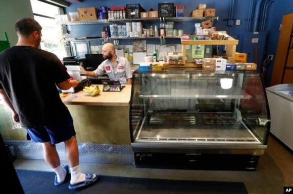 Karyawan James Lawrence melayani pelanggan di supermarket Replenish di Ann Arbor (AP Photo/Paul Sancya)