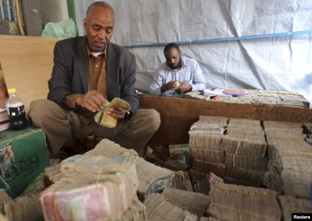 FILE - A money changer waits for customers at a local bureau where $100 U.S. dollars exchange for 750,000 Somaliland shillings in Hargeysa.