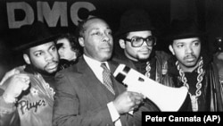 Principal Joe Clark stands with the rap group Run-DMC before the group gave a concert at the school in support of Clark's way of running his school. (AP Photo/Peter Cannata)