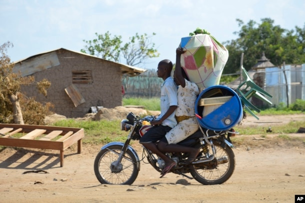 FILE - A couple flees on motorbike from the Jabel area of Juba, South Sudan, July 16, 2016.