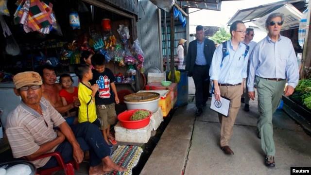 Ngoại trưởng Hoa Kỳ John Kerry (phải) đến thăm ấp Kiến Vàng nằm bên bờ sông Mekong, Việt Nam, ngày 15 tháng 12 năm 2013.