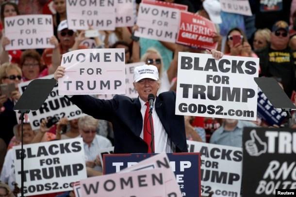 """川普及其支持者在佛罗里达州的竞选大会上举着标语""""妇女支持川普""""""""黑人支持川普""""(2016年10月12日)"""