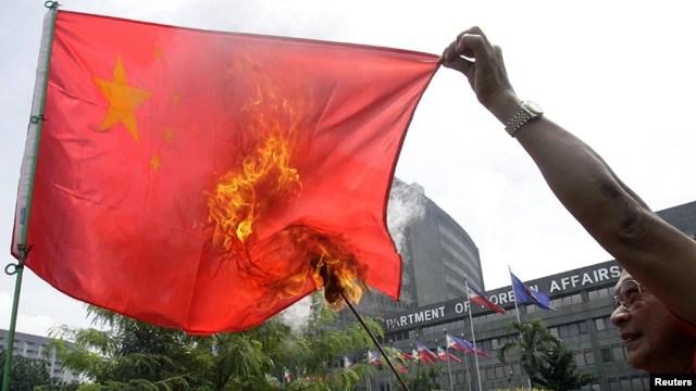 Một người biểu tình đốt cờ Trung Quốc ở Manila. Hà Nội dường như dang rộng vòng tay với với các quốc gia khác cùng chí hướng như Philippines nhằm ngăn chặn sự lấn lướt của Bắc Kinh trên biển Đông.