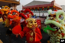 Members of Cambodia's Chinese community perform a traditional lion dance during the lunar new year Monday, Feb. 4, 2019, in front of Royal Palace, in Phnom Penh, Cambodia. (AP Photo/Heng Sinith)