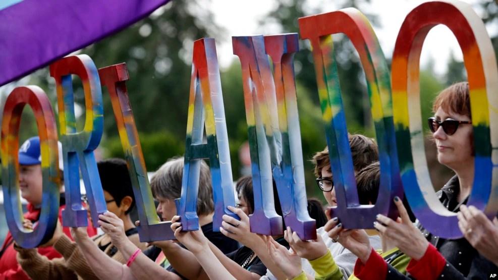 Cộng đồng LGBT cầm biểu ngữ tưởng nhớ các nạn nhân thiệt mạng trong vụ xả súng ở Orlando.