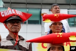 Protesters, wearing boat-shaped paper hats and mock missiles, join others in a rally at the Chinese Consulate to protest China's alleged continued militarization of the disputed islands in the South China Sea known as Spratlys, Feb. 10, 2018.