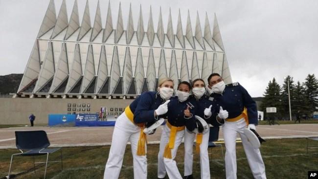 Frente a la capilla de la Academia de la Fuerza Aérea de EE.UU., cadetes con máscaras faciales posan para los fotógrafos después de su ceremonia de graduación. Sábado 18 de abril de 2020, Colorado Springs, Colorado.