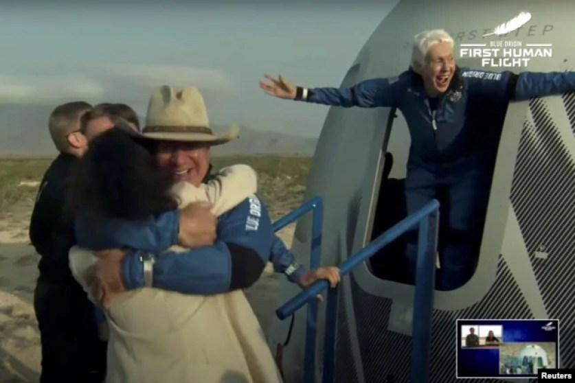 Pengusaha miliarder Jeff Bezos dan penerbang wanita Wally Funk, keluar dari kapsul setelah penerbangan suborbital tanpa pilot pertama di dunia dengan roket New Shepard Blue Origin, mendarat di dekat Van Horn, Texas, AS, 20 Juli 2021. (REUTERS)