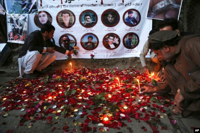 FILE - Afghan residents light candles to pay tribute to Afghan journalists killed in a suicide attack in Kabul, Afghanistan, May 3, 2018.