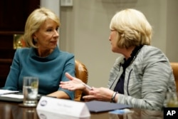 Secretary of Education Betsy DeVos, left, speaks with Commissioner Pam Stewart of the Florida Department of Education before a meeting between President Donald Trump and state and local officials to discuss school safety.
