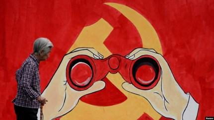 Một người phụ nữ đi bên cạnh bức tường mang biểu tượng của Đảng Cộng sản trên một con phố ở Thượng Hải, Trung Quốc.