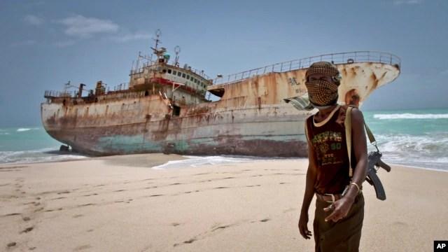 Perompak Somalia dengan penutup wajah berdiri dekat kapal nelayan Taiwan yang awaknya telah dibebaskan setelah pembayaran tebusan, di Hobyo, Somalia. (Foto: Dok)