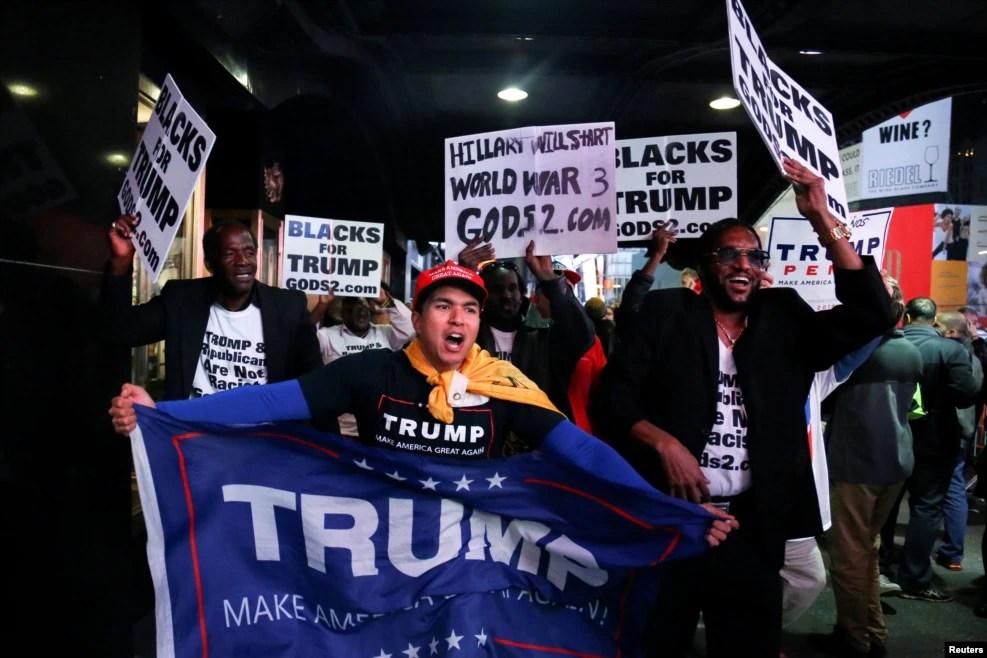 """纽约时报广场上,川普支持者欢呼,有人手持标语""""黑人支持川普""""""""克林顿会发动第三次世界大战""""(2016年11月8日)"""