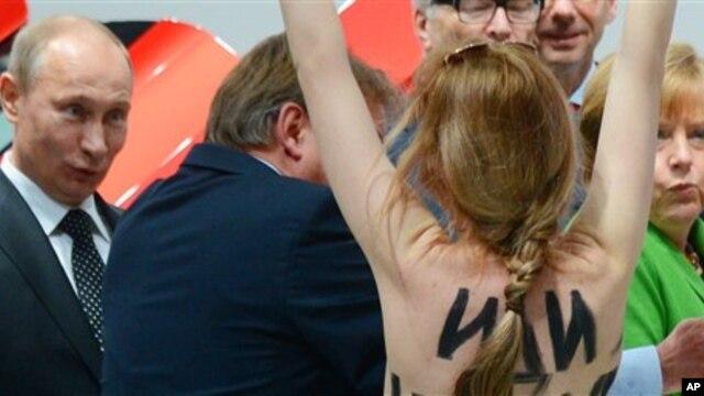 Một người biểu tình ngực trần viết những lời chống Tổng thống Nga trên lưng tiến về hướng Tổng thống Putin (trái) và Thủ tướng Merkel, 8/4/13