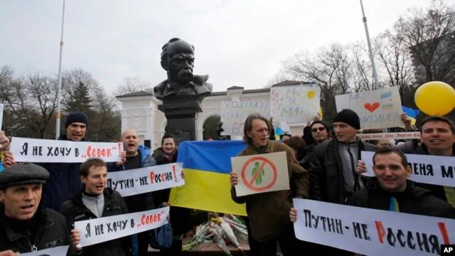 Người biểu tình bên cạnh một bức tượng của nhà thơ Ukraina Taras Shevchenko trong một cuộc biểu tình chống lại sự chia cắt đất nước tại Simferopol, Crimea, ngày 9/3/2014.