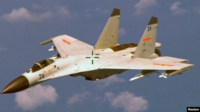 Chiến đấu cơ Trung Quốc J-11 bay gần máy bay trinh sát P-8 Poseidon của Hải quân Mỹ, khoảng 215 km (135 dặm) về phía đông đảo Hải Nam của Trung Quốc. (Ảnh: Bộ Quốc phòng Mỹ/chụp ngày 19/8/2014).