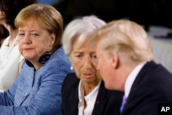 FilE - German Chancellor Angela Merkel watches as President Donald Trump talks with IMF Managing Director Christine Lagarde during the Gender Equality Advisory Council breakfast during the G-7 summit, June 9, 2018, in Charlevoix, Canada.