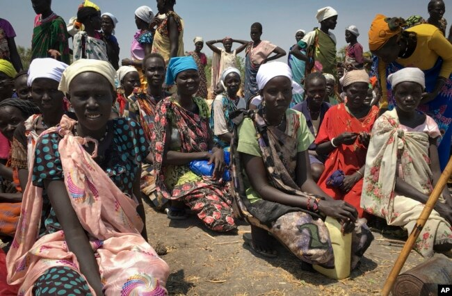 FILE - Women sit in line waiting to receive food distributed by the World Food Program in Padeah, South Sudan, Feb. 18, 2017. South Sudanese girls are being held as sexual slaves, and women, young and old, gang raped as part of a systematic campaign by the South Sudanese government, a new U.N. report alleges.