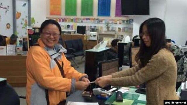 Bà Sơ Mỹ Linh (trái) hoàn tất việc chuyển hộ khẩu ở Cao Hùng, ngày 21/1/2016 (Ảnh chụp từ trang CNA).