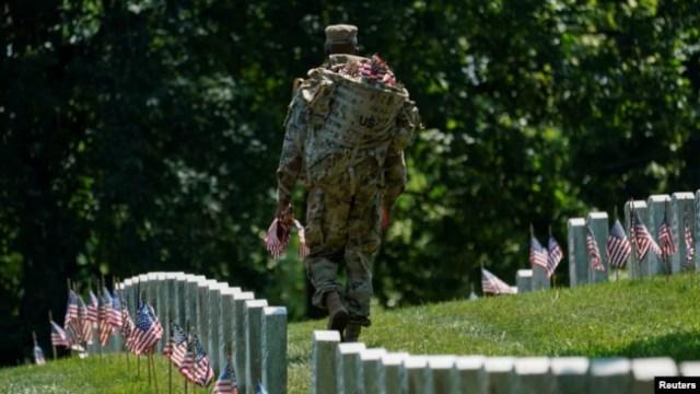 """Una oficial de la """"Vieja Guardia"""" participa en """"Flags-In"""", un evento anual donde se coloca una pequeña bandera estadounidense frente a las lápidas de miembros del servicio de EE.UU. enterrados en el Cementerio Nacional de Arlington,en Virginia. Foto: Reuters."""