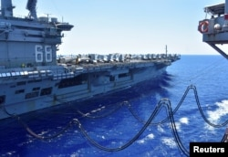 The U.S. Navy aircraft carrier USS Nimitz receives fuel from the Henry J. Kaiser-class fleet replenishment oiler USNS Tippecanoe during an underway replenishment in the South China Sea July 7, 2020.