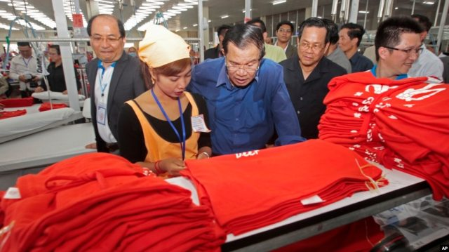 FILE: Prime Minister Hun Sen, center, leans over a garment worker during a visit to a factory outside of Phnom Penh, Cambodia, Aug. 30, 2017.