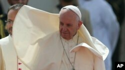 Wind blows Pope Francis' cape during an official welcome ceremony at the Abu Dhabi Presidential Palace, United Arab Emirates, Monday, Feb. 4, 2019.