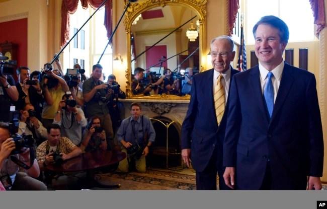 El candidato a la Corte Suprema Brett Kavanaugh, a la derecha, y el senador Chuck Grassley, republicano por Iowa, segundo desde la derecha, caminan frente a la prensa después de posar para fotógrafos en el Capitolio, en Washington, el 10 de julio de 2018.
