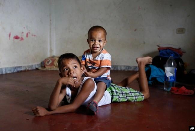 En esta foto del 27 de junio de 2018, los niños migrantes venezolanos juegan en el piso de la casa sin muebles que sus padres están alquilando y compartiendo durante los últimos dos años con otra familia venezolana en Cúcuta, Colombia.