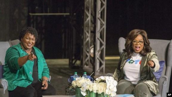 Oprah Winfrey y la candidata a la gobernación de Georgia, Stacey Abrams, saludan a una multitud reunida, en el Teatro Jennie T. Anderson.
