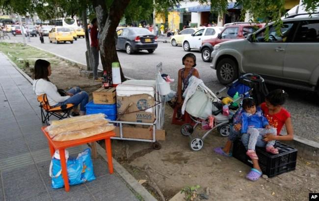 En esta foto del 28 de junio de 2018, la migrante venezolana Maria Fuentes, en el centro, se sienta con su hija, a la izquierda, y dos nietas mientras vende bocadillos en la vereda de Cúcuta, Colombia.