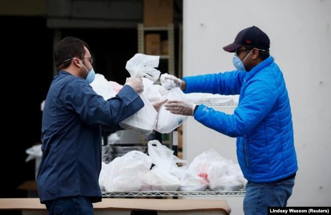 Ilustrasi. Hazim Macky mengambil makan berbuka puasa dari Mohamed Saleem yang disiapkan untuk masyarakat di luar Asosiasi Muslim Puget Sound pada hari pertama Ramadan di tengah wabah corona di Redmond, Washington, AS, 24 April 2020. (Foto: Reuters/Lindsey)