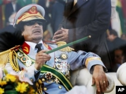 FILE - Libyan leader Moammar Gadhafi gestures with a green cane as he takes his seat behind bulletproof glass for a military parade in Green Square, Tripoli, Libya, Sept. 1, 2009.