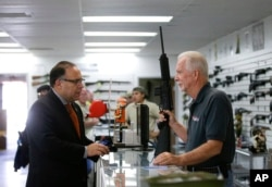 FILE - Sales associate Mike Conway, right, shows Paul Angulo a semiautomatic rifle at Bullseye Sport gun shop in Riverside, Calif., Dec. 9, 2015.