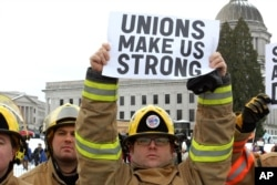 FILE - A firefigher holds a pro-union sign at a rally in Olympia, Wash., Feb. 26, 2011.