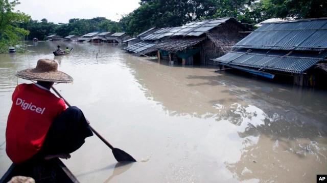 Một người đàn ông chèo thuyền gần ngôi nhà bị ngập lụt ở Nyaung Tone, đồng bằng châu thổ Irrawaddy, khoảng 100 km về phía tây nam Yangon, Myanmar ngày 5/8/2015.