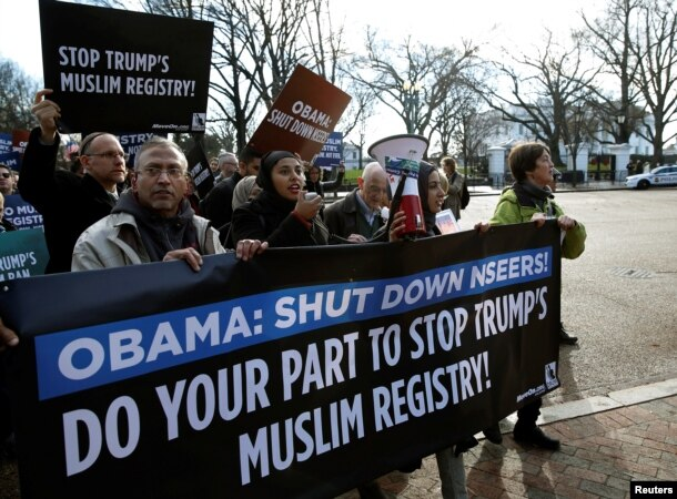 FILE - Members of Join MoveOn and DRUM march past the White House during a protest to shut down the existing Muslim registry program NSEERS in Washington, Dec. 12, 2016.