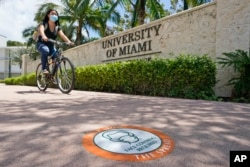 A cyclist, wearing a mask to prevent the spread of the new coronavirus, rides by an entrance to the University of Miami, Tuesday, Aug. 25, 2020, in Coral Gables, Fla. (AP Photo/Wilfredo Lee)