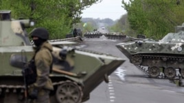 A Ukrainian soldier stands guard in front of armored personnel carriers at a check point near the village of Malynivka, southeast of Slovyansk, in eastern Ukraine, April 29, 2014
