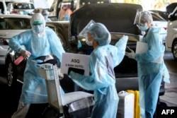Petugas mengenakan alat pelindung diri (APD) mendisinfeksi bagasi penumpang penerbangan internasional yang tiba di bandara Suvarnabhumi, Bangkok, Thailand, sebelum membawa mereka ke hotel untuk Karantina Negara Alternatif (ASQ) wajib 14 hari, 16 November 2020.